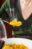 Paella dans la fourchette de la femme avec la robe verte Photos libres de droits