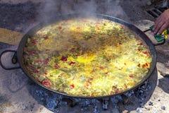Paella de poulet, de légumes et de riz Le plat espagnol national de la Paella dans une grande poêle est fait cuire sur un feu ouv Photo libre de droits