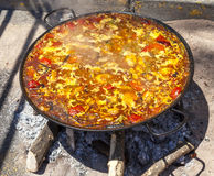 Paella de poulet, de légumes et de riz Le plat espagnol national de la Paella dans une grande poêle est fait cuire sur un feu ouv Photos libres de droits