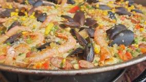 Paella española con el arroz, los camarones amarillos y los mejillones cocinando en el mercado de la comida Cámara de enfoque Fes almacen de video