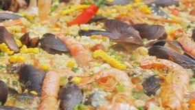 Paella española con el arroz, los camarones amarillos y los mejillones cocinando en el mercado de la comida Cámara de la toma pan almacen de video