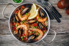 Paella espagnole de fruits de mer avec des moules, des crevettes et des saucisses de chorizo dans la casserole traditionnelle sur Photos libres de droits