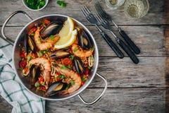 Paella espagnole de fruits de mer avec des moules, des crevettes et des saucisses de chorizo dans la casserole traditionnelle sur Image stock