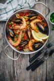 Paella espagnole de fruits de mer avec des moules, des crevettes et des saucisses de chorizo dans la casserole traditionnelle sur Photo libre de droits