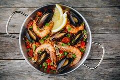 Paella espagnole de fruits de mer avec des moules, des crevettes et des saucisses de chorizo dans la casserole traditionnelle sur Photographie stock