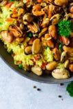 Paella espagnole traditionnelle de fruits de mer en riz de casserole, pois, crevettes, moules, calmar sur le fond concret gris-cl Images libres de droits