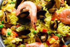 Paella espagnole traditionnelle de fruits de mer en riz de casserole, pois, crevettes, moules, calmar sur le fond concret gris-cl Image libre de droits