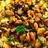 Paella espagnole traditionnelle de fruits de mer en riz de casserole, pois, crevettes, moules, calmar sur le fond concret gris-cl Photo stock