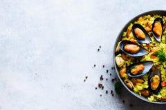 Paella espagnole traditionnelle de fruits de mer en riz de casserole, pois, crevettes, moules, calmar sur le fond concret gris-cl Photographie stock libre de droits