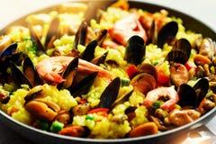 Paella espagnole traditionnelle de fruits de mer en riz de casserole, pois, crevettes, moules, calmar sur le fond concret gris-cl Photos libres de droits