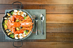 Paella with fresh lobster, clams, mussels and lime Stock Photos