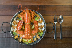 Paella with fresh lobster, clams, mussels and lime Stock Images