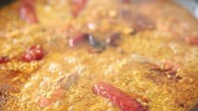 Paella het koken op een elektrisch fornuis stock footage