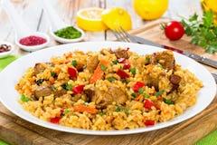 Paella med kött, peppar, grönsaker och kryddor på maträtt Arkivbilder