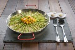 Paella med kammusslor, sparris i traditionell panna arkivbilder