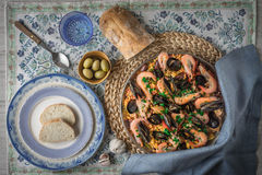 Paella on the metal plate on the beautiful napkin with tableware and bread top view Stock Photography