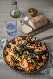 Paella in the metal plate on the wooden table Stock Photos