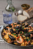 Paella in the metal plate on the wooden table  vertical Stock Photo