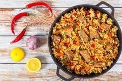 Paella mit Fleisch, Pfeffer, Gemüse und Gewürzen lizenzfreie stockbilder