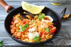 Paella mit Reis und Meeresfrüchten in einer Bratpfanne Stockfoto