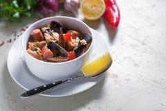 Paella na placa branca com arroz do açafrão, ervilhas, camarões, mexilhões, calamar, carne Paella do marisco, prato espanhol trad Foto de Stock Royalty Free