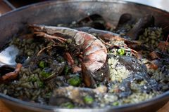 Paella negra in the pan. Tradition Spanish dish - valencian seafood arozza negra Paella in authentic pan paellera Royalty Free Stock Image