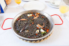 Paella negra on the pan, white table Royalty Free Stock Image