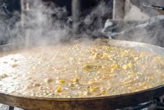 Paella in a paella pan. Cooking on a low heat. You see the smoke coming out stock photo