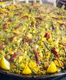 Paella in a paella pan. Cooking on a low heat. You see the smoke coming out. It´s a vertical picture royalty free stock photos