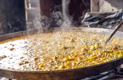 Paella in a paella pan. Cooking on a low heat. You see the smoke coming out stock images