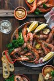Paella pan with roasted tiger shrimps and many dishes, bread and wine Stock Photos