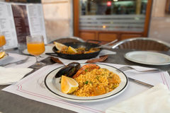 Paella on the plate in street cafe Stock Photo