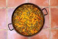 Paella rice recipe Mediterranean Spain round pan. On clay floor royalty free stock photo