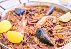 Paella savoureuse de fruits de mer dans la casserole noire - plat traditionnel de riz espagnol Photos stock
