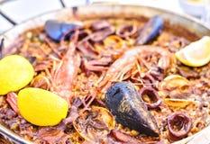 Paella savoureuse de fruits de mer dans la casserole noire - plat traditionnel de riz espagnol Photos libres de droits