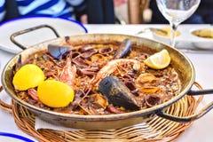 Paella savoureuse de fruits de mer dans la casserole noire - plat traditionnel de riz espagnol Images stock