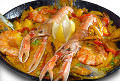 Paella with seafood in a frying pan. On a white background stock images