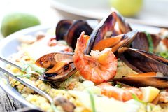 Paella with seafood. Traditional spanish food closeup on wooden table. stock photography