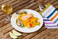 Paella served in plate on wooden table stock photos