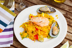 Paella served in plate on wooden table Royalty Free Stock Image