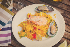 Paella served in plate on wooden table Royalty Free Stock Photos