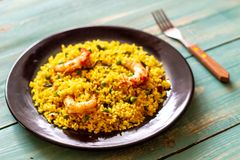 Paella with shrimp on a blue wooden background royalty free stock photos