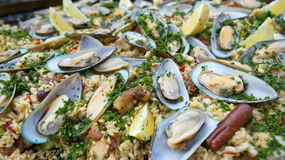 Paella, tasty up close with mussels. A tasty macro shot of the Spanish favorite Paella, with sausage on the side, lemon wedges, chicken, rice, and cilantro Royalty Free Stock Photo