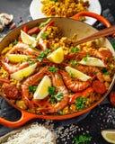 Paella tradicional en la cacerola de fritada con el pollo, las gambas, el chorizo picante, el limón y el vidrio de vino blanco Foto de archivo libre de regalías