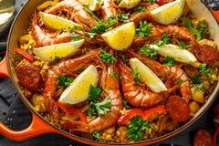 Paella tradicional en la cacerola de fritada con el pollo, las gambas, el chorizo picante, el limón y el vidrio de vino blanco Imagen de archivo