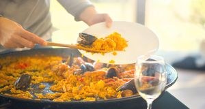 Paella. Traditional spanish food. Person putts seafood paella from the fry pan to plate. Paella with with mussels and squids. Paella. Traditional spanish food royalty free stock photography