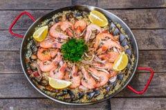 Paella traditionnelle de fruits de mer dans la casserole de friture sur une vieille table en bois, vue supérieure Photos libres de droits