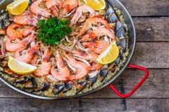 Paella traditionnelle de fruits de mer dans la casserole de friture sur une vieille table en bois, vue supérieure Image libre de droits