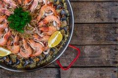 Paella traditionnelle de fruits de mer dans la casserole de friture sur une vieille table en bois, vue supérieure Images stock