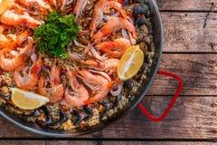 Paella traditionnelle de fruits de mer dans la casserole de friture sur une vieille table en bois, vue supérieure Photographie stock libre de droits
